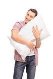 Vertical shot of a young man hugging a pillow Royalty Free Stock Photo