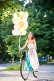 Happy woman holding baloons while riding bicycle. Vertical shot of a young woman cycling in the park laughing happily holding bunch of colored baloons happiness Royalty Free Stock Photo