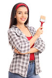 Vertical shot of a young woman holding a paintbrush Royalty Free Stock Image