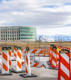 Vertical Sidewalk Closed sign and road safety poles on a paved road under repair. In the background is a modern building with skybridge and snowy mountain royalty free stock photos