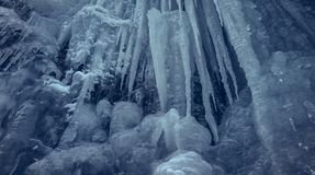 Vertical icicles in a cavern. Vertical slippery steep ice wall with long icicles in a cavern. Frozen waterfall stream stock images