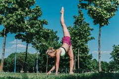 Vertical split on the grass. Girl doing vertical twine on grass in the park in hot summer Stock Photos