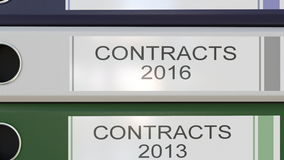 Vertical stack of multicolor office binders with Contracts tags different years stock footage