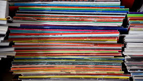 Vertical stacks of colorful magazines. Vertical stacks of colorful paper magazines between other piles of magazines and books Royalty Free Stock Photos