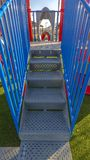 Vertical Stairs going up a slide overlooking mountain and bright sky on a sunny day. The stairs has blue handrails that cast shadows on the lush lawn royalty free stock photos