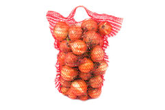 Vertical standing string bag of bright onions Royalty Free Stock Photo