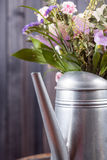 Vertical still life flowers in watering can dark background Royalty Free Stock Images