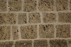 Old stone wall vertical walling. A vertical stone wall with gray stripes divided into squares of different shapes Stock Images