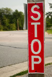 Vertical Stop Sign. A red, vertical pedestrian stop sign on the street Royalty Free Stock Image