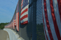 Vertical stripes of American flags on sunny side of highway overpass fence Stock Photo