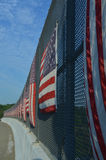 Vertical stripes of American flags on sunny side of highway overpass fence Royalty Free Stock Photos