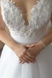Vertical strzelający młoda Kaukaska panna młoda w koronkowej odkrywczej ślubnej sukni, mieniu i seansie, jej ręki krzyżować dumni fotografia stock
