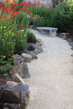 Vertical Summer Path. A curved garden path edged with stones winds through a perennial garden with crocosmia and dasies Royalty Free Stock Images