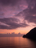Vertical sunset. Red sky, calm sea and rocky coast. With crescen Royalty Free Stock Image