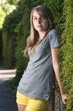 Vertical teenage girl stands near vines in the shade. Outside Royalty Free Stock Photo