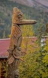 Vertical - um totem cinzelado de madeira no interior de Alaska imagens de stock