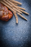 Vertical version ears of wheat and sweet bun Stock Photos