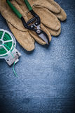 Vertical version green garden wire and secateurs on glove Royalty Free Stock Photos