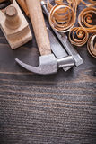 Vertical version of planer claw hammer metal. Chisels and wooden curled shavings on vintage wood board construction concept Stock Images