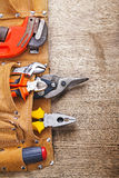 Vertical version working tools in toolbelt on wooden board.  Royalty Free Stock Image