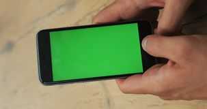 Vertical video. Man hand holding and using smartphone in the street green screen mockup chromakey blur background. Checking news notification map gps chatting stock footage