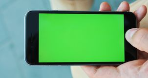 Vertical video. Man hand holding and using smartphone in the street green screen mockup chromakey blur background. Checking news notification map gps chatting stock video footage