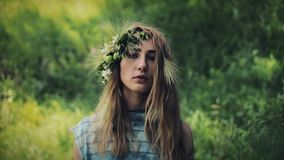 Vertical video. Portrait of mystical girl in the woods hold a ritual. She dressed in long dresses with wreath on the