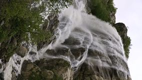 Vertical video. Slow motion water falls from a huge rock. Waterfall in the natural environment in cloudy weather with. Light rain stock footage