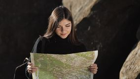 Vertical video. Travelling to the mountains. Hiker woman holds old map standing on the top of the rock. The tourist stock footage