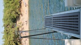 Vertical video of yacht stern against beach.