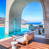 Vertical view of arch pool terrace on summer resort Greece. Arch pool terrace on summer luxury resort  with beautiful Mediterranean sea view, Greece. Square Royalty Free Stock Photography