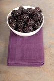 Vertical view of blackberries in a white bowl on a purple napkin Royalty Free Stock Photo