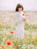 The vertical view of the bride holding and looking at the poppy in the spring field. Royalty Free Stock Photos
