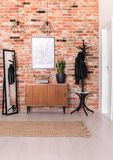 Vertical view of classic hall with brick wall, real photo. Vertical view of classic hall with brick wall, wooden shelf, mirror and map on the wall, real photo royalty free stock photography