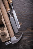 Vertical view of claw hammer wooden planer and. Flat chisels on vintage wood board construction concept Stock Image