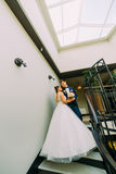 The vertical view of the happy newlyweds standing on the stairs. The vertical view of the happy newlyweds standing on the stairs Royalty Free Stock Image