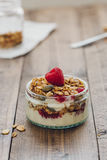 Vertical View of Homemade Baked Granola with Yogurt and Fresh Raspberries. Vertical food scene of small glass ramekin layered with granola, natural yogurt and Royalty Free Stock Photos