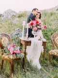 The vertical view of the hugging newlyweds behind the blurred wedding table set. Royalty Free Stock Photography