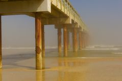 Long wooden pier stretching out to a foggy ocean horizon. Vertical view of long wooden pier in St. Augustine Beach, Florida, stretching out and disappearing into royalty free stock photos