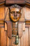 Vertical View of an Old Clapper With Egyptian Faces on a Decorat. Ed Wooden Old Door. Bari, South of Italy Royalty Free Stock Photo