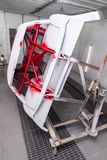 Vertical view of painting in red and black color of the inside of the frame of the car disassembled after the accident in the. Workshop for body repair and royalty free stock images