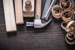 Vertical view of planer hammer chisels wooden. Studs and curled shavings on vintage wood board construction concept Stock Photography