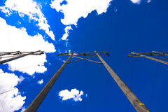 Vertical view of power lines. And brilliant sky overhead Royalty Free Stock Photos