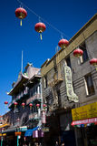 Vertical view of Red Chinese Lanterns hanging across a street in San Francisco's Chinatown, with blue sky above. Many of the buildings in this area were built Royalty Free Stock Photo