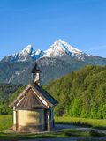 Vertical view of small chapel and snowy summit of Watzmann mount Stock Photo