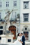 Vertical wedding portrait of the handsome groom softly kissing the gorgeous bride in the cheek while sitting on the old. Fountain in the city center Stock Image