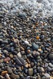 Vertical wet bright shining colored pebble stones and sea foam Stock Photography