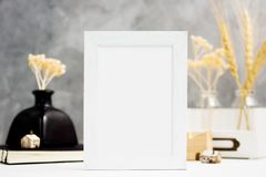 Vertical white Photo frame mock up with dry plants in vase, notebook and wooden houses on shelf. Scandinavian style. Text space Stock Image