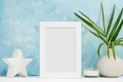 Vertical white Photo frame mock up with plants in vase, ceramic decor on shelf. Scandinavian style. Text space stock images