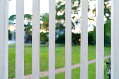 Vertical White Steel Fence Grille front of Garden royalty free stock photography